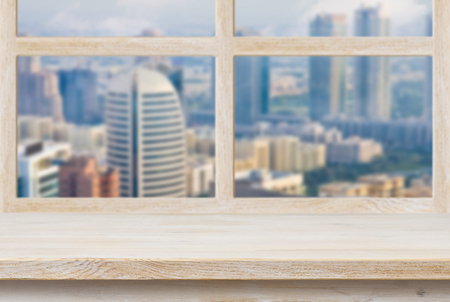 Wooden sill over blurred city view trough window