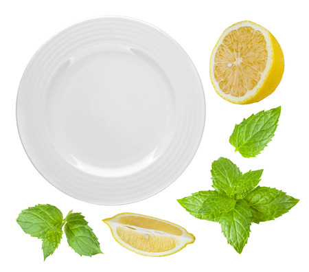 Top view of isolated white plate with lemon and mint
