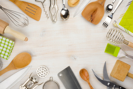 Kitchen utensils and cutlery background with copy space in center