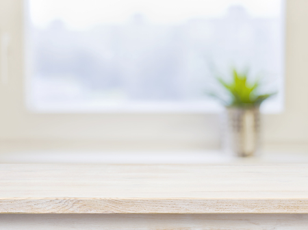 Photo pour Wooden table on defocuced winter window background - image libre de droit