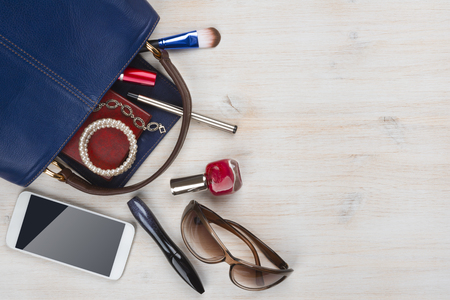 View on women bag stuff with copyspace on wooden background