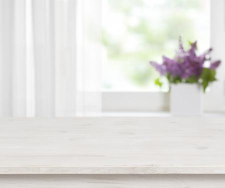 Foto de Wooden table on defocused window with purple flower pot background - Imagen libre de derechos