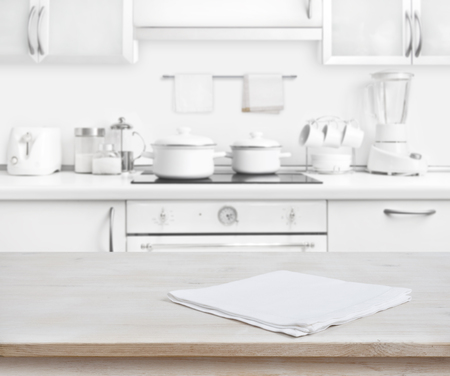 Photo pour Wooden table with towel on blurred white modern kitchen background - image libre de droit