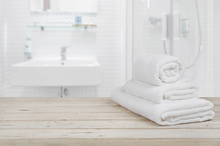 Photo pour Blurred bathroom interior background and white spa towels on wood - image libre de droit