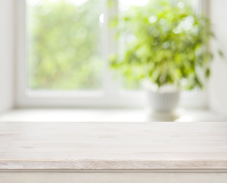 Photo for Light wooden table on defocuced spring window background - Royalty Free Image