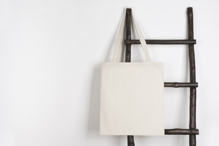 Photo pour Fabric cloth shopping bag mockup hanging on vintage wooden stepladder - image libre de droit