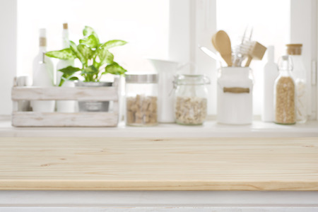 Photo pour Wooden table over blurred kitchen window sill for product display - image libre de droit