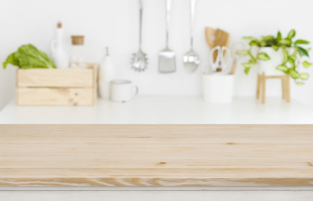 Photo pour Blurred kitchen workplace with empty wooden table top in front - image libre de droit