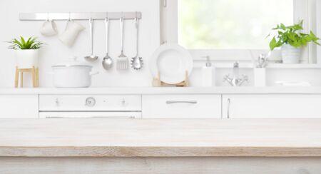 Photo pour Wooden table top on defocused kitchen room and window - image libre de droit