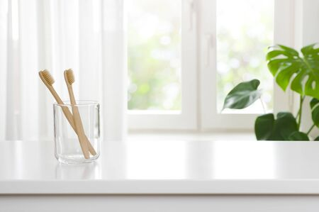 Photo pour Two wooden toothbrushes in glass on blurred window background - image libre de droit
