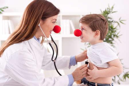 Smiling female doctor clown listen patient heart