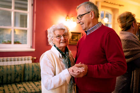 Older couple dancing in the room and enjoying their time together