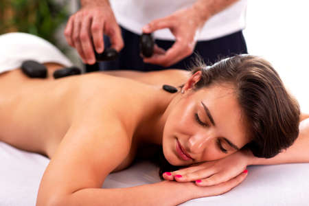 Photo for Pretty girl having a stone massage therapy and enjoying herself - Royalty Free Image