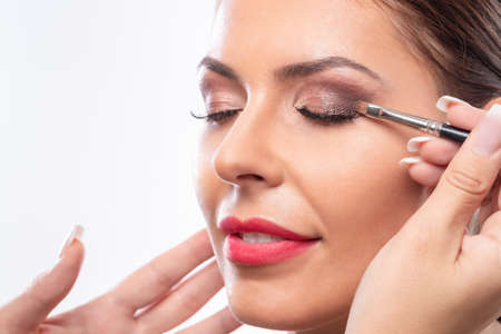 Photo for Close up of a pretty face while applying makeup, matching skin tan - Royalty Free Image