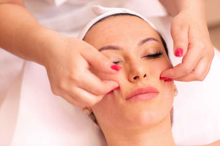 Photo pour Woman undergoing a facial madero massage in welness center performed only with fingers of a masseuse - image libre de droit
