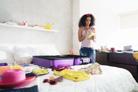 Foto für Cute African American Girl Packing Bag For Holiday And Travel - Lizenzfreies Bild