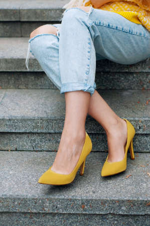 Street city fashion outfit with yellow poncho, high heels and boyfriend jeans