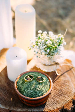 Foto de Outdoor table setting on wooden table with candles, wedding rings and bridal bouquet - Imagen libre de derechos