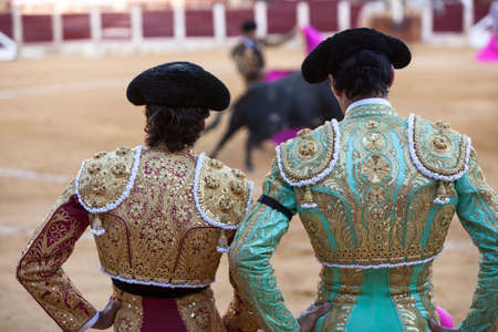 Ubeda, Jaen province, SPAIN - 29 september 2010  Spanish Bullfighters looking bullfighting, the Bullfighter on the left dressed in suit of lights of colors red and gold and the right color pistachio and gold in Ubeda, Jaen provincia, Andalusia, Spain