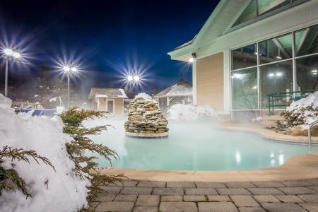 Foto de hot tubs and ingound heated pool at a mountain village in winter at night - Imagen libre de derechos