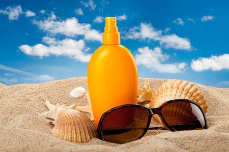 Suntan oil and dark glasses on the beach