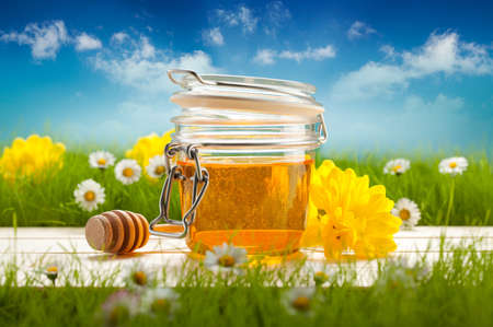 Jar of honey and spring flowers
