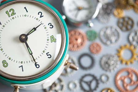 Photo pour Old retro vintage alarm clock and watch gears on gray table - image libre de droit