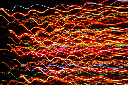 Wavy multicolored glowing lines against a dark background (long exposure shot)