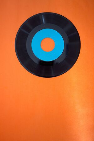 vintage 45 rpm record on an orange background