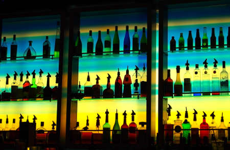 A multi-color glass wall behind a bar illuminates a collection of alcohol bottles of many interesting shapes in silhouette standing on glass shelves in dark, ambient bar at night.