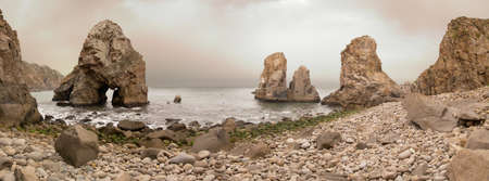 Boulder beach at Cabo da Roca in the early morning under an overcast sky of dust clouds. Autumn colors. Sintra, Portugal.