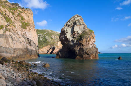 Malhada do Ourical boulder beach and huge rock near Cape Roca  Blue ocean and sky  Sintra, Portugal