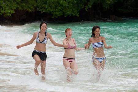 Three girls run on the beach