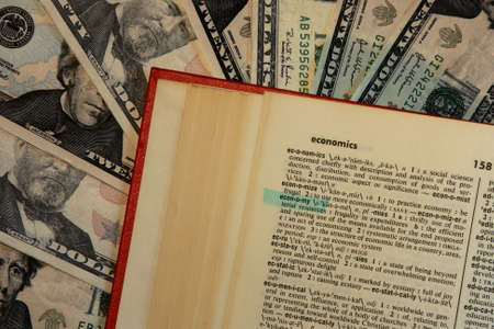 dictionary with economy highlighted with money background