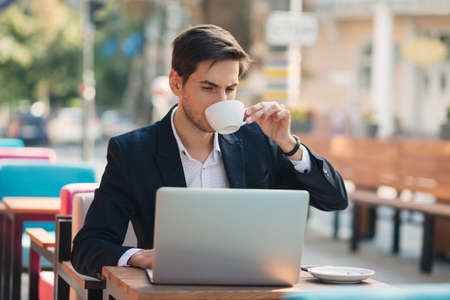 Young entrepreneur working on laptop, at the table on colorful cafe terrace and enjoying coffee holding the cup in his hands. Freelancer, in casual jacket, unbuttoned shirt looking to laptop screen.