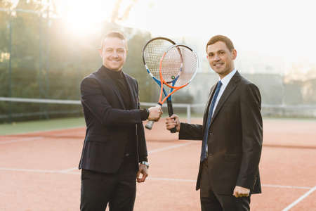Two businessmen in suits holding tennis rackets crossed looking to camera, announcing their intention to win, smiling being ready to compete. Business, sport, competition, partners.