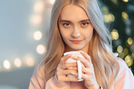 A pretty young woman making a wish while drinking a hot cup of milk, coffee waiting holidays with blurred lights on tree in the background at home. Portrait beautiful blond girl holding a white mug.の写真素材