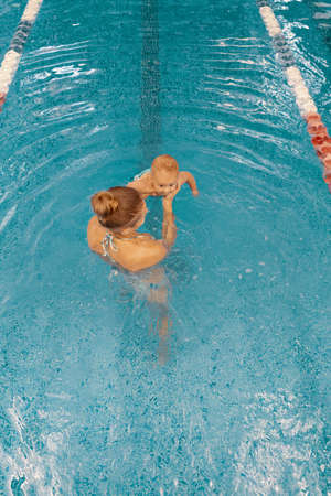 Photo for Young mother and her baby enjoying a baby swimming lesson in the pool. Child having fun in water with mom - Royalty Free Image