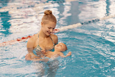 Photo pour Young mother and her baby enjoying a baby swimming lesson in the pool. Child having fun in water with mom - image libre de droit