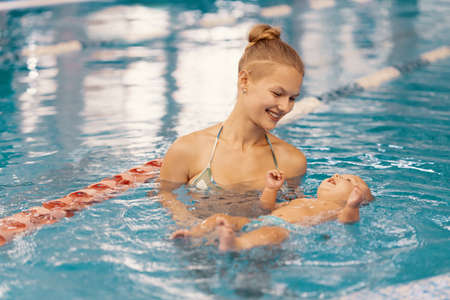 Young mother and her baby enjoying a baby swimming lesson in the pool. Child having fun in water with mom