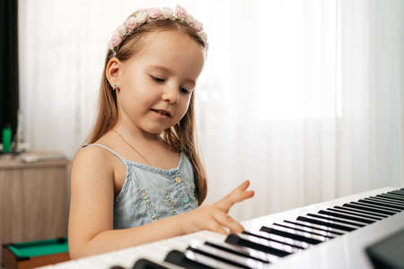 Photo pour Lovely little girl sitiing at digital piano. Playing keyboard, focused kid have activity at home. Hobby - image libre de droit