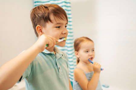 Photo pour Indoor portrait of cute kids brushing their teeth in the bathroom, happy family and dental hygiene - image libre de droit