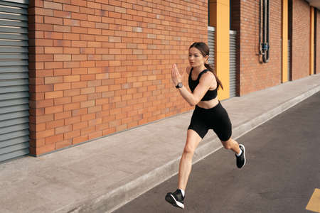 Foto de Young woman sprinting in the morning outdoors. Top view of female runner working out in the city. - Imagen libre de derechos