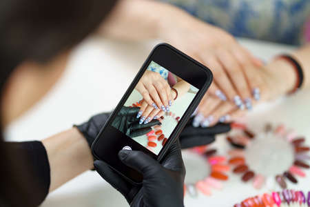Photo pour Manicurist takes a photograph of her work, beautiful woman manicure, with a smartphone - image libre de droit