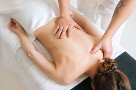 Photo pour Top view of male masseur doing back massage to young unrecognizable woman in spa salon. Professional physiotherapist with strong hands making movements with hand along the spine toward head. - image libre de droit