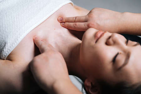 Photo pour Close-up top view of young woman lying down on massage table with closed eyes during shoulder and neck massage at spa salon. Male masseur professionally massaging shoulders on black background. - image libre de droit