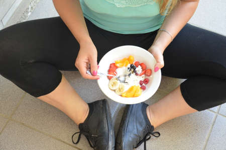 Photo pour Young woman is resting and eating a healthy salad after a workout. Fitness and healthy lifestyle concept. - image libre de droit