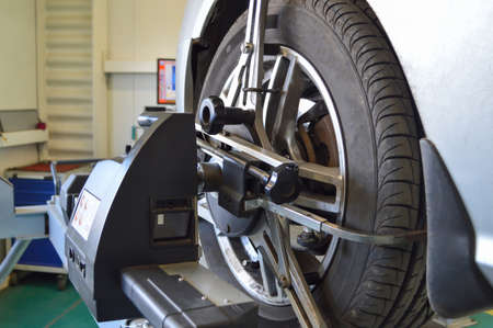 Photo pour Camber-convergence adjustment stand sensor mounted on the front left wheel of a gray car in a car repair shop - image libre de droit