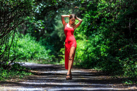 Photo pour Beautiful Model In Red Dress Posing In The Tropical Jungle - image libre de droit