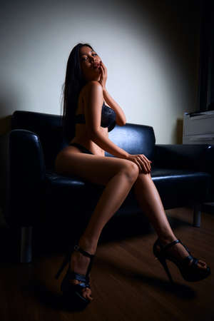 Photo pour Sexy young asian woman in black underwear sitting on a leather sofa - image libre de droit